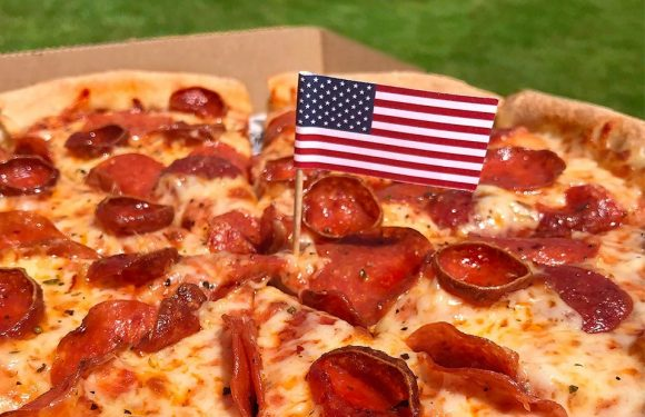 Pepperoni Pizza photo with an American flag on a toothpick, stuck into the pizza