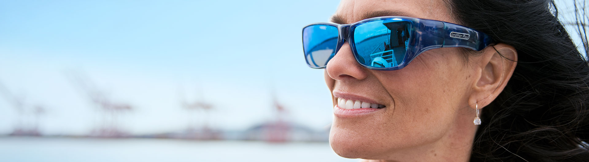 A woman wears a large pair of sunglasses designed to fit over prescription frames