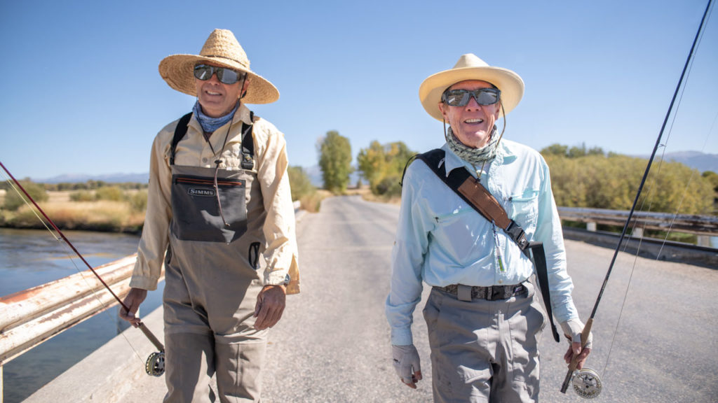 Flyfishers cross a Wyoming river in polarized fitover sunglasses