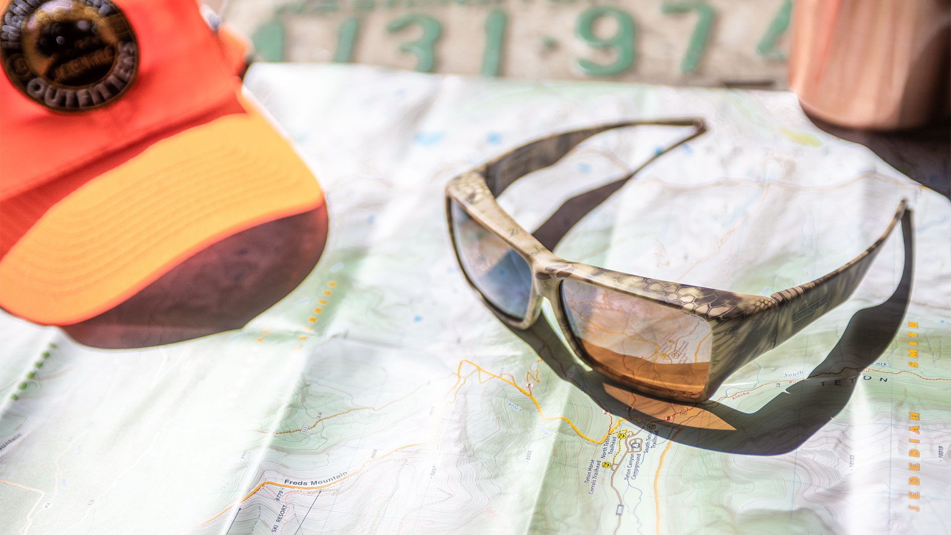 A pair of fit over sunglasses rests on a map