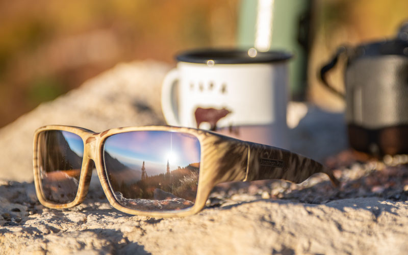 A mountain scene is reflected in the lenses of Jonathan Paul fitover sunglasses.