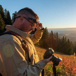 A man reviews the back of his camera screen wearing fitover eyewear