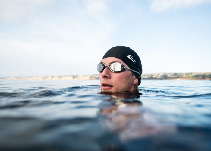 Image of man in water wearing Leader Swim Goggles and Swim Accessories