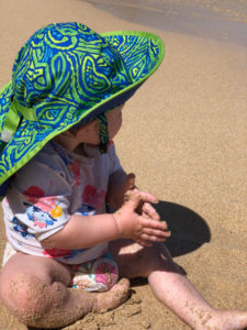 a child plays in the sand on the beach