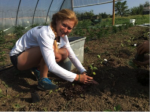 Marissa Porter kneeling down to plant something in the soil
