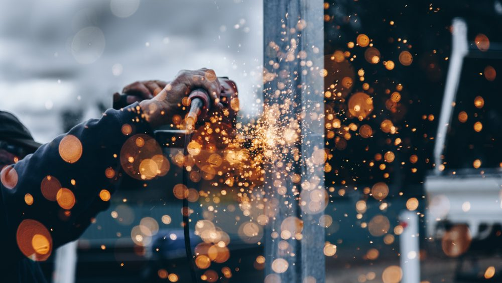 skilled worker operating machinery with blurred sparks in Canada