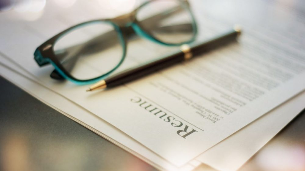 resume with glasses and pen blurred