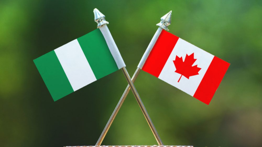 Canadian and Nigerian flags on blurred green background
