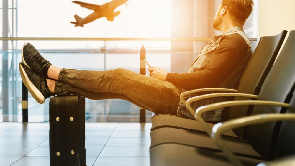 man sitting in airport with legs on suitcase holding a cellphone watching plane take off