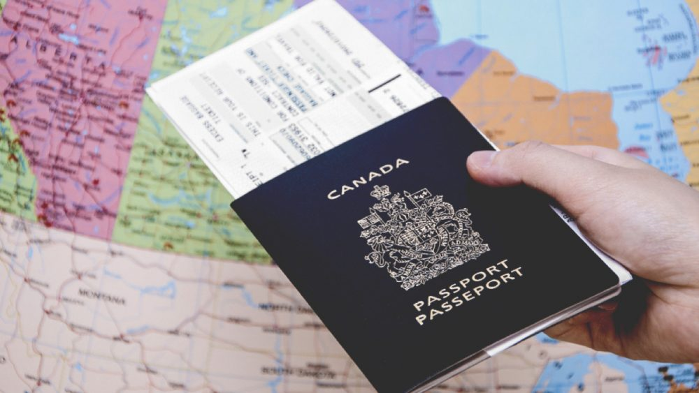 Canadian passport with plane ticket and map