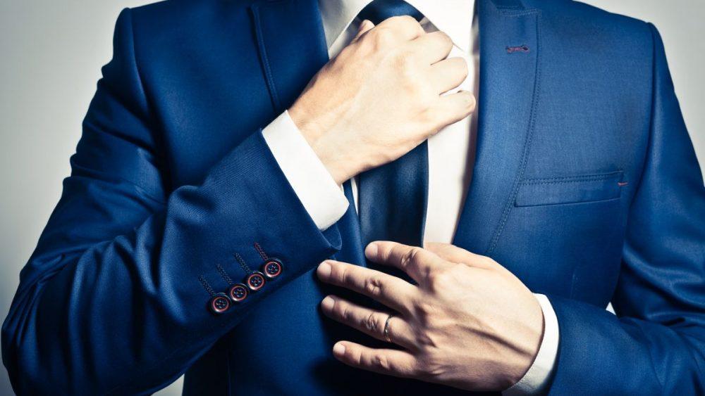 businessman adjusting blue tie wearing blue suit