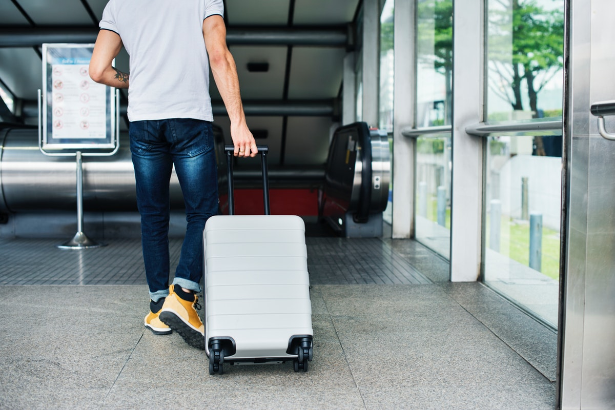 adult man arriving at Canadian airport with suitcase