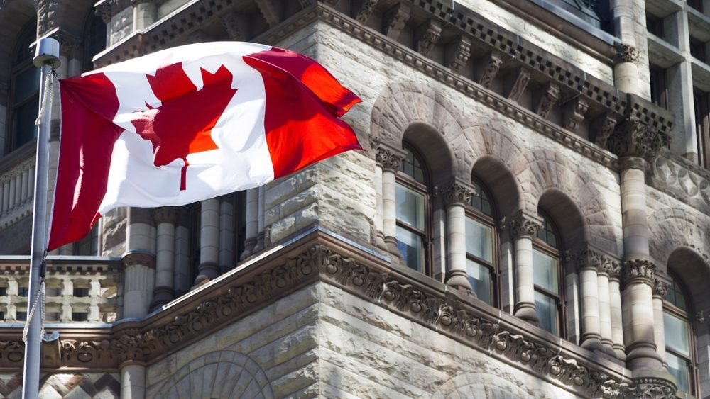 Canadian flag blowing in the wind in front of building