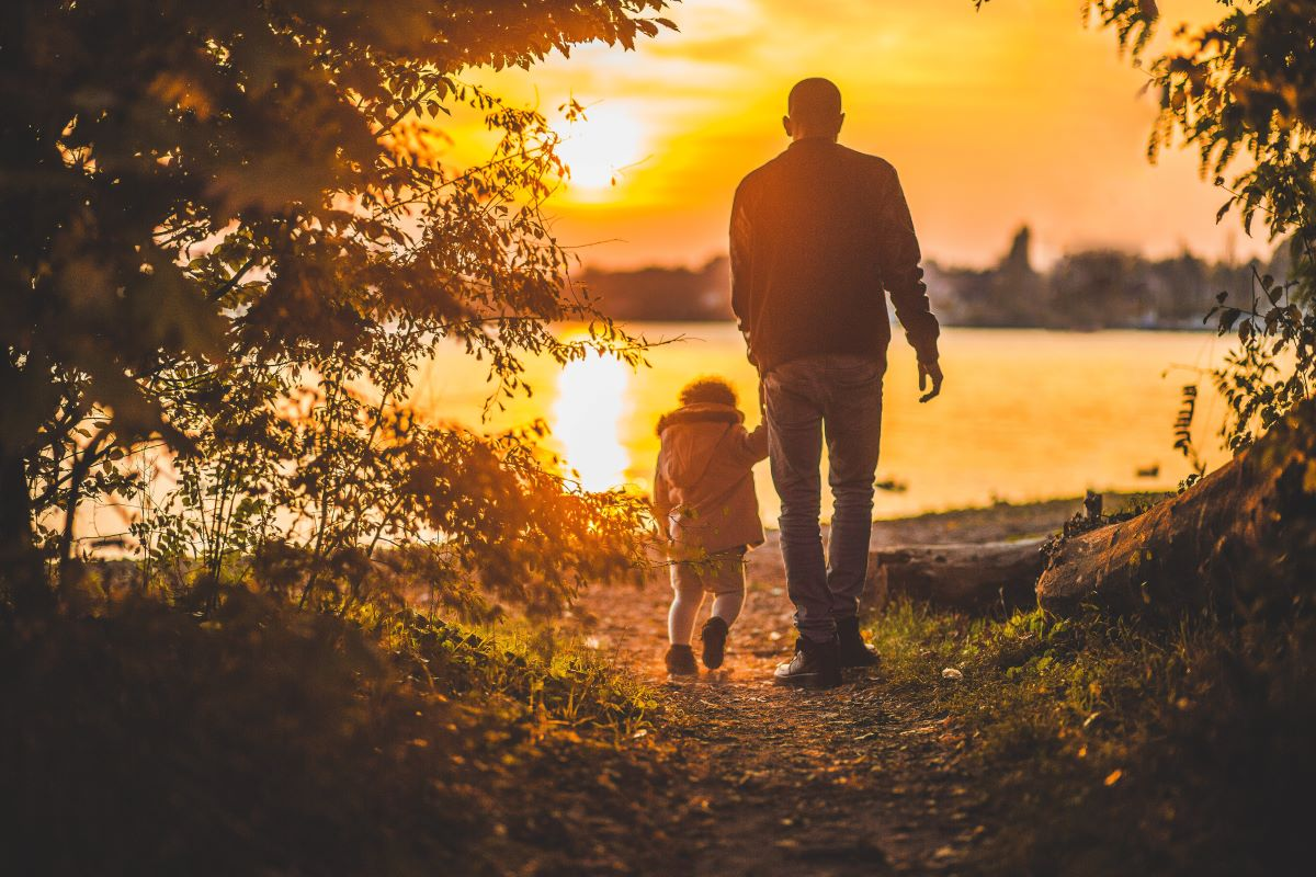 father and child walking in nature at sunset