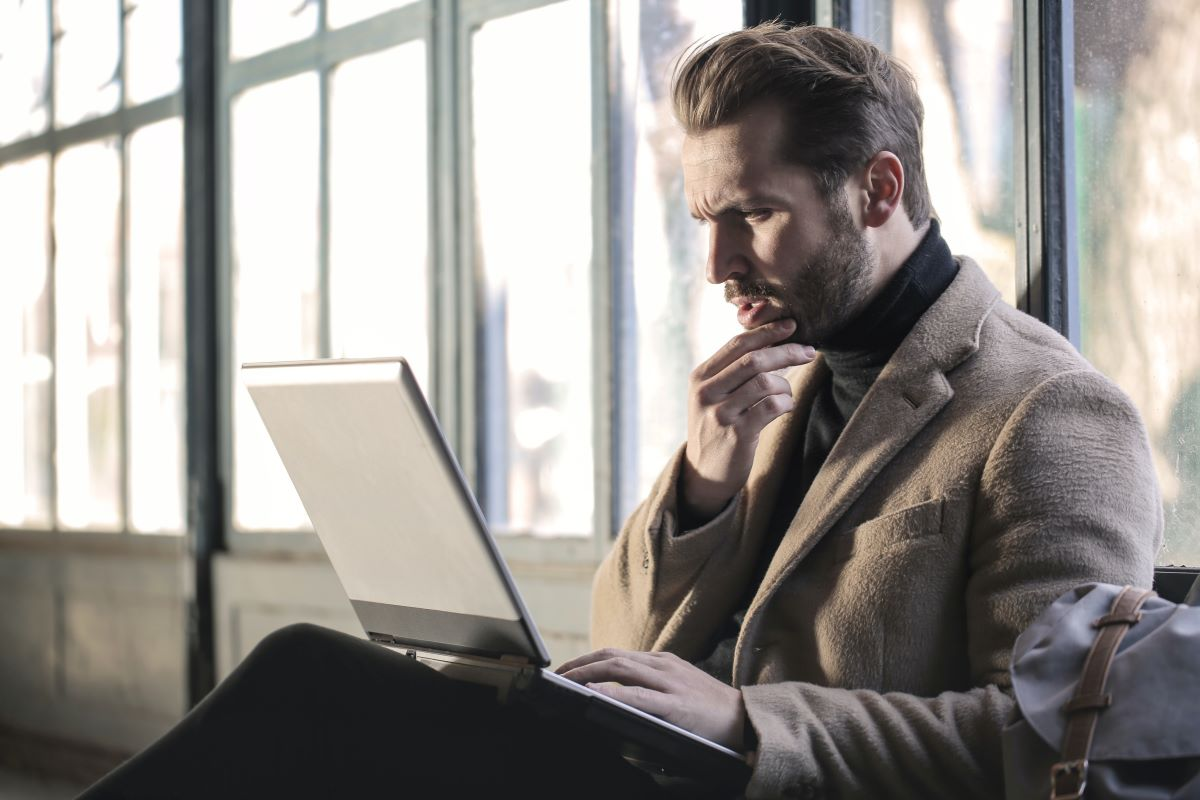 Man thinking with laptop on his lap | Latest Express Entry Draw Has Lowest CRS of 2020