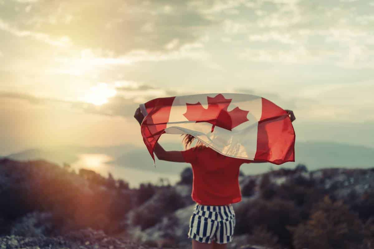 girl holding Canada flag at sunset | 10 reasons to Apply for a Canada Visa in 2020