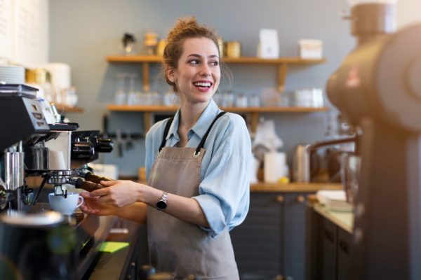 happy female student working as a barista in coffee shop