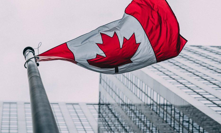 Canadian Flag blowing in wind between buildings