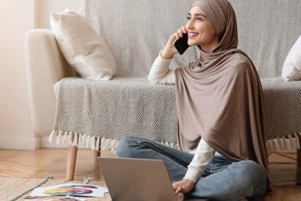happy Muslim woman sitting on floor speaking on mobile