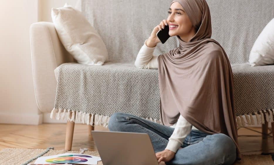 happy Muslim woman sitting on floor speaking on mobile