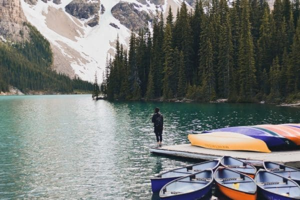 man standing on wooden pier looking at Rockies mountains in Canada | immigrate to Canada