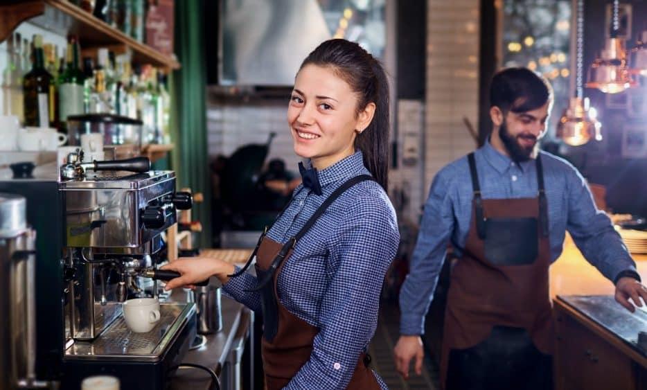 Female barista smiling while making a espresso