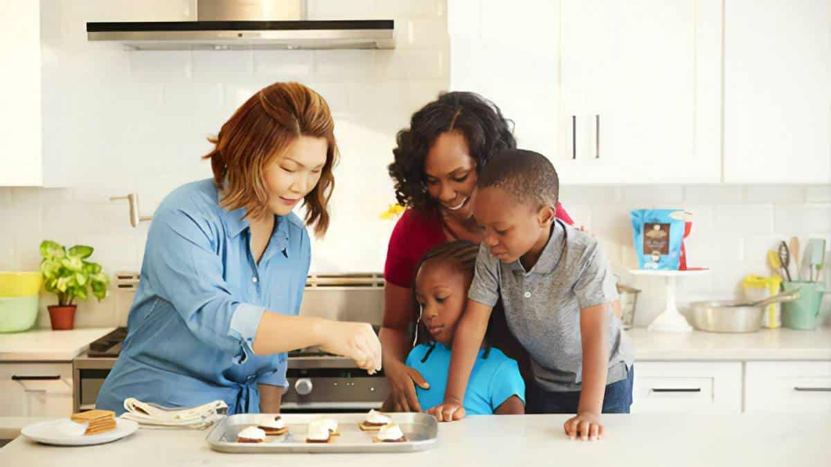 Two mother of different ethnicity baking with their kids