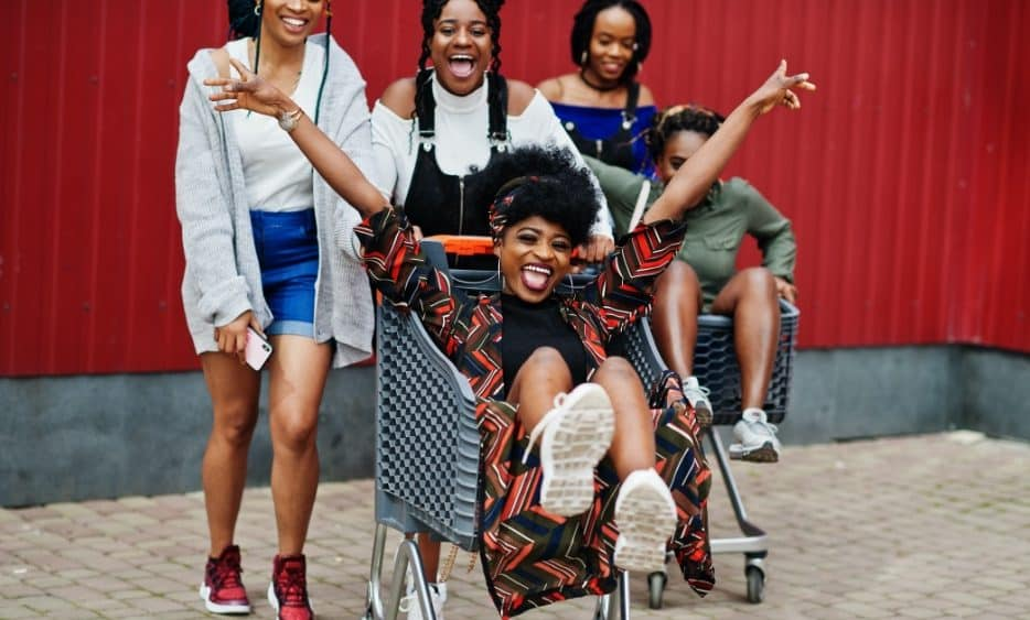 Beautiful African girls having fun in a shopping stroller