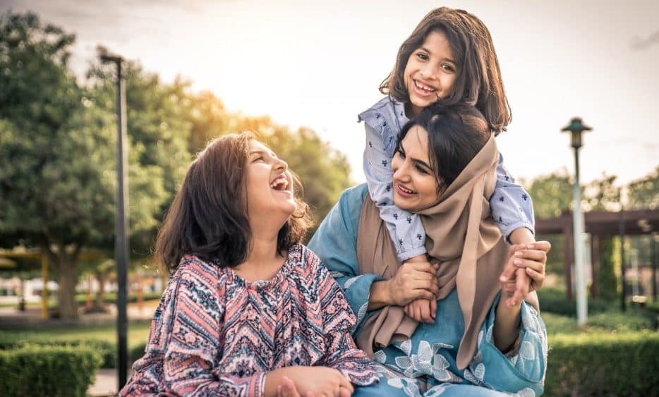 Indian woman with children laughing in park | immigrate to Canada from India