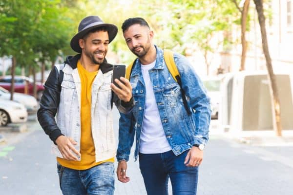 Two young Mexican guys walking on the street looking at a phone screen