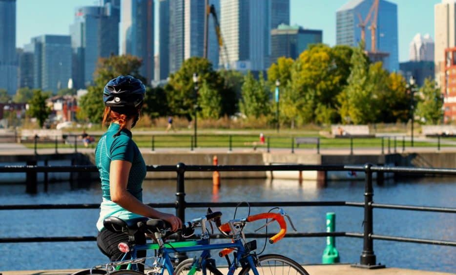 Woman on bicycle in front of cityscape