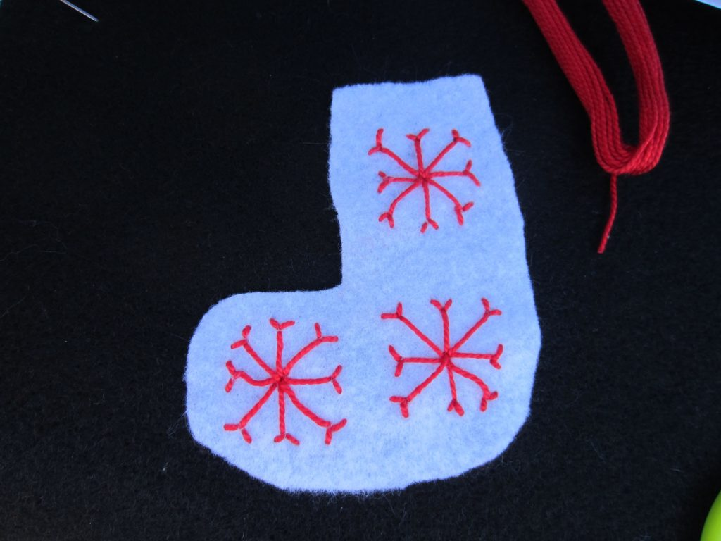 Three snowflakes are stitched on the ornament