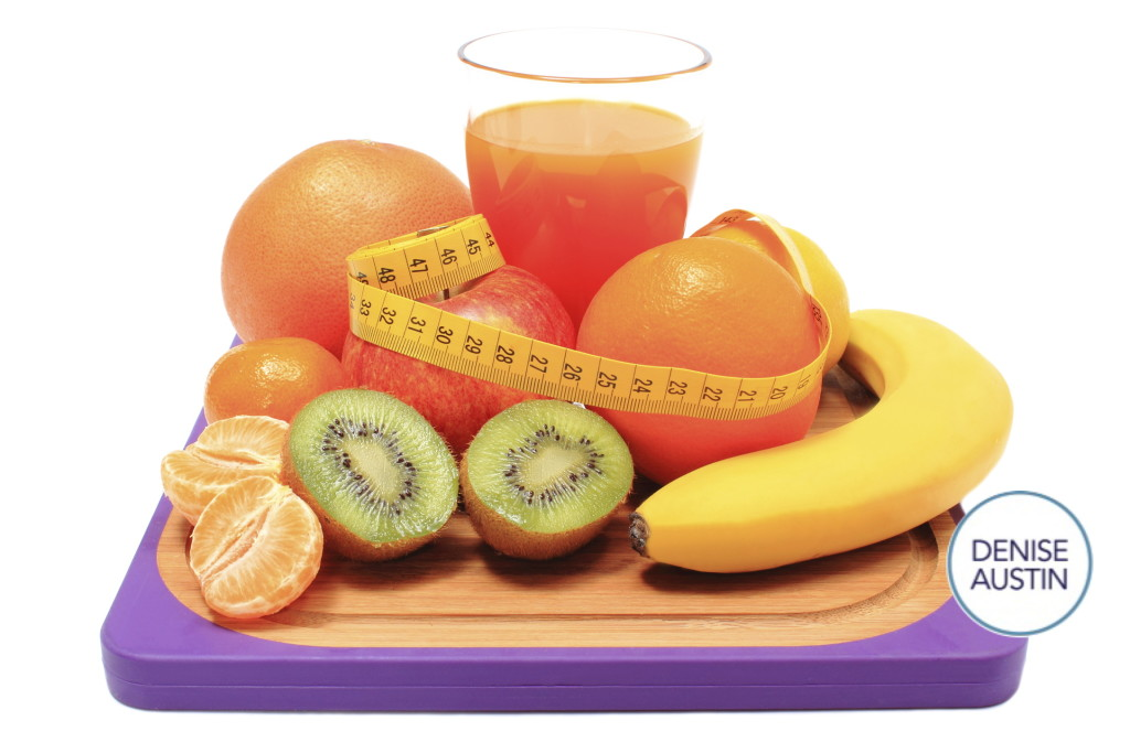 Fresh ripe natural fruits, glass of juice and tape measure on cutting board, concept for slimming, healthy nutrition and strengthening immunity