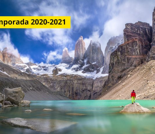 Viajero observa montañas desde laguna color turquesa