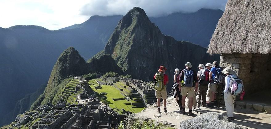 Grupo de viajeros observando restos arqueológicos de machu picchu
