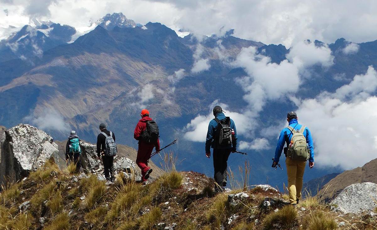 Viajeros caminan frente a montañas