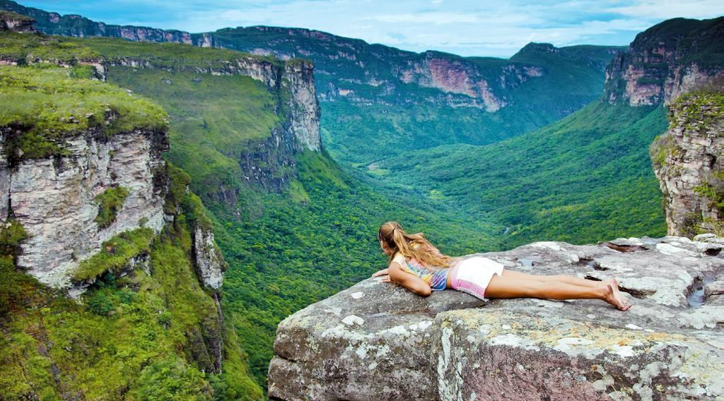 Mujer descansa sobre roca frente a paisaje