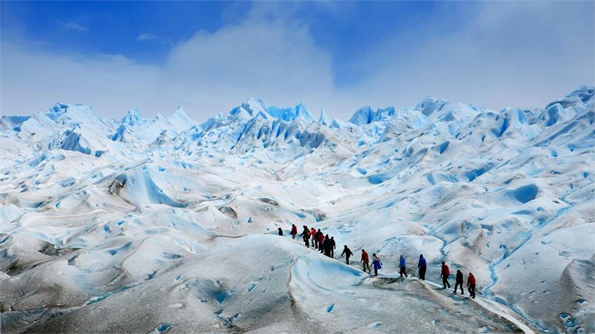 viajeros realizan caminata sobre glaciar