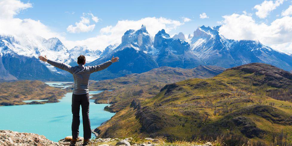 viajero extiende sus brazos mientras mira las montañas