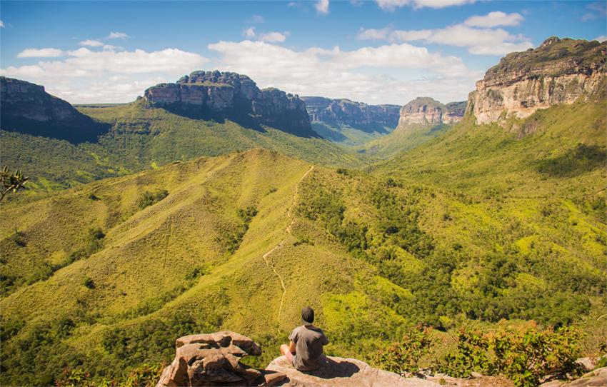 Hombre observa rutas y paisaje montañoso y verde