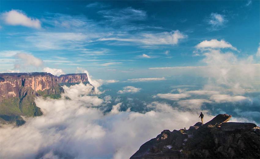 Viajero observa desde la cima de un monte