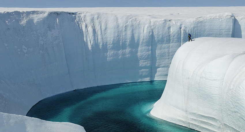 persona parada sobre el hielo de un glaciar