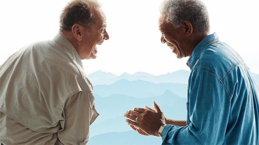 Dos hombres riendo frente a paisaje montañoso