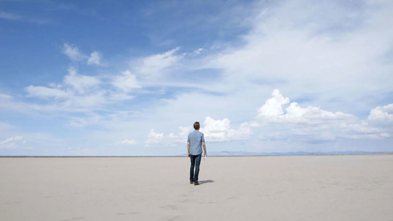 Hombre frente a desierto desolado