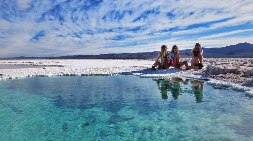 Adolescentes sentadas frente a laguna turquesa en baltinache