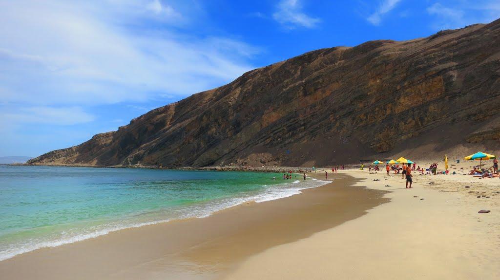 Playa tranquila frente a roca gigante