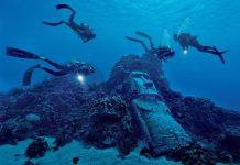 Buzos alrededor de moai sumergido