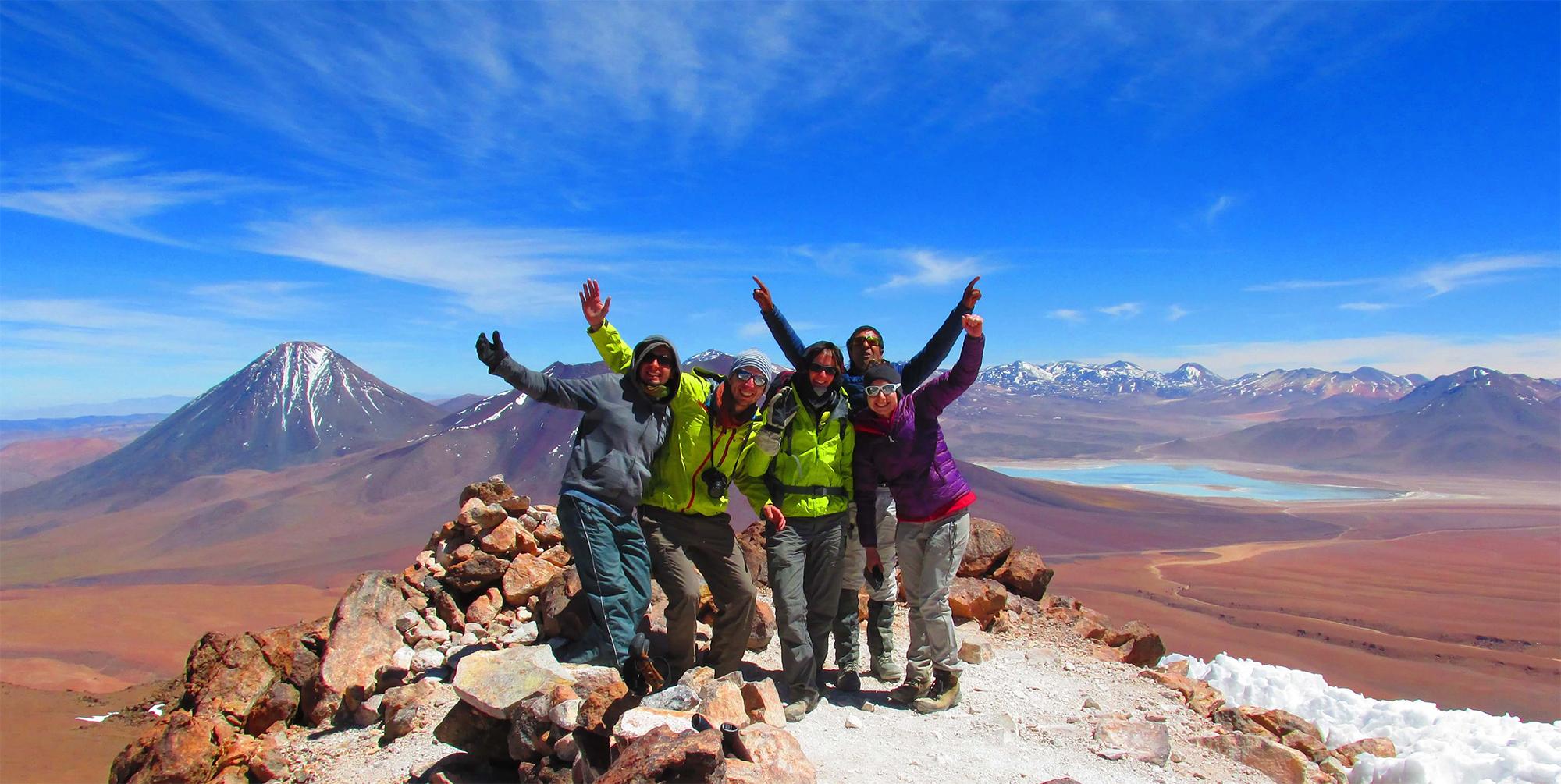 Viajeros en cima de volcan y otros volcanes al fondo del paisaje