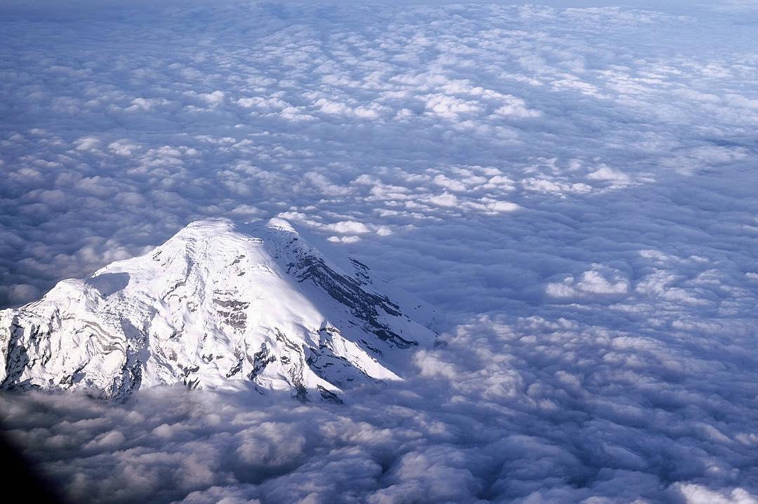 Volcan nevado por encima de las nubes