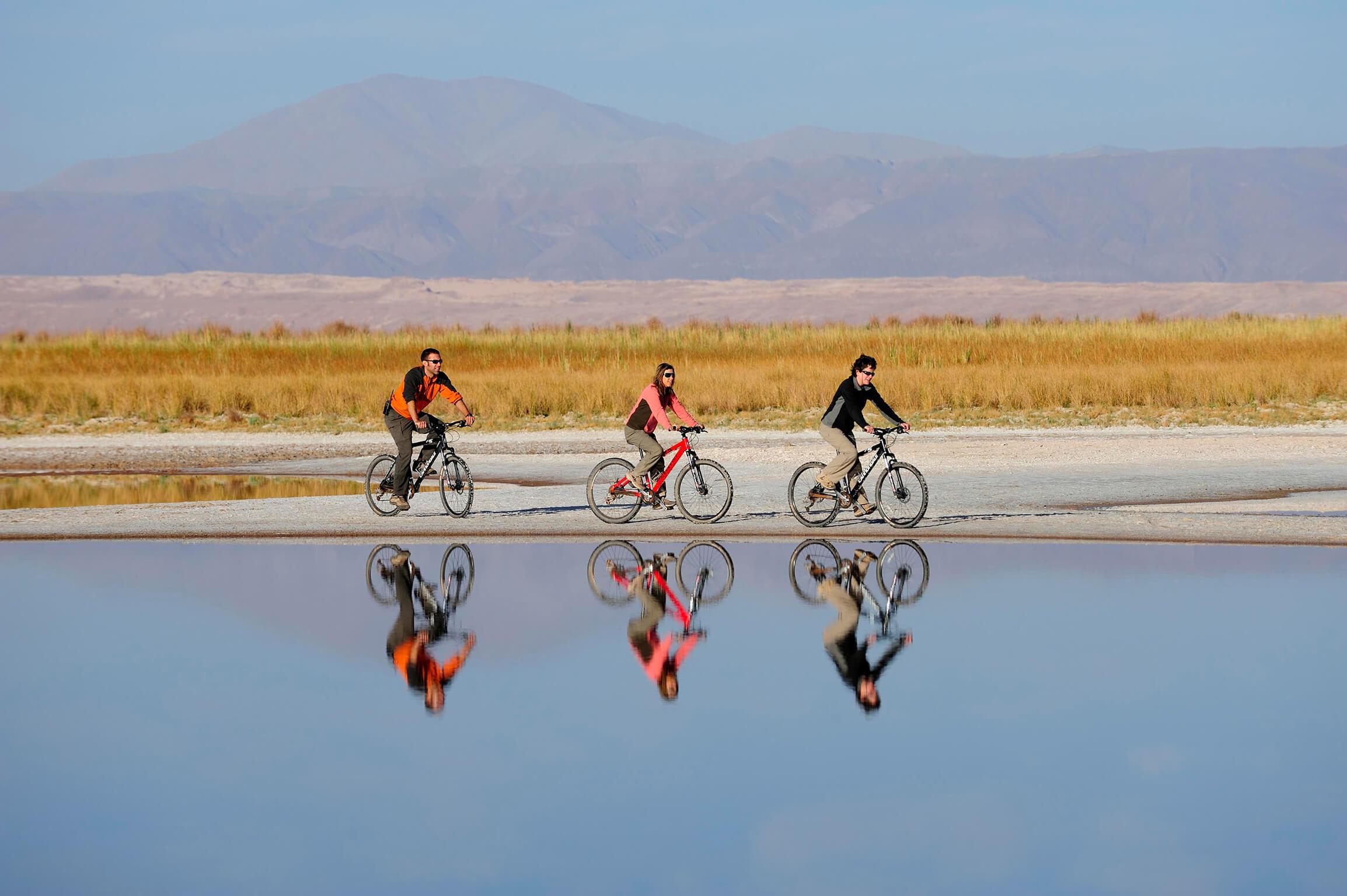 Tres ciclistas frente a una laguna